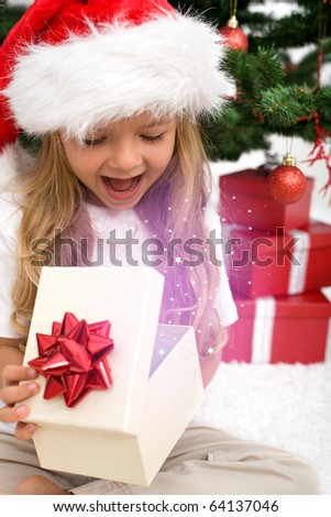 Excited little girl opening christmas present with magical glow in front of the fir tree - closeup - stock photo