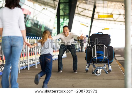 excited little girl running to her father at airport after a long wait with mother - stock photo