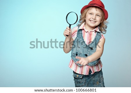 Excited little girl with magnifying glass, isolated on a blue background - stock photo
