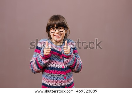 Excited little nerdy girl is showing thumb up.Nerdy girl with thumb up
