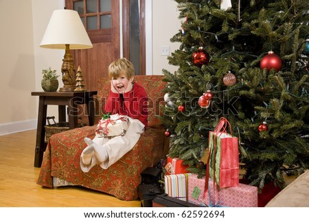 Excited little 4 year old boy with present by Christmas tree