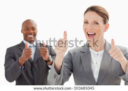 Excited looking businesspeople with their thumbs up - stock photo