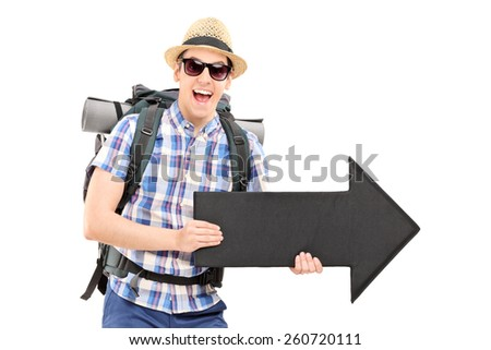 Excited male tourist holding a black arrow pointing right isolated on white background - stock photo