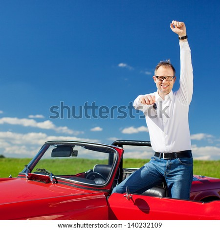 Excited man celebrating ownership of a cabriolet standing with the hood down and door open raising his arm in jubilation and holding out the key in sunny fresh countryside - stock photo