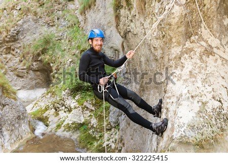 Excited man climbing cliff in canyon with rope. - stock photo