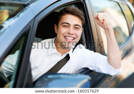 Excited man driving a car - stock photo