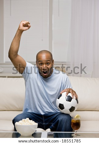 Excited man holding soccer ball cheering and celebrating soccer success on television