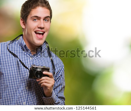 Excited Man Holding Vintage Camera against a nature background