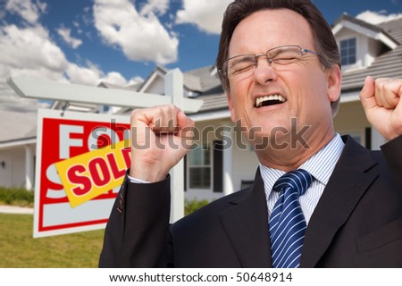 Excited Man in Front of Sold Real Estate Sign and Beautiful New House. - stock photo