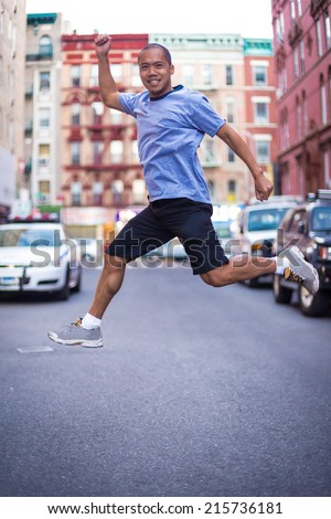 Excited man jumping in middle of street in the city - stock photo