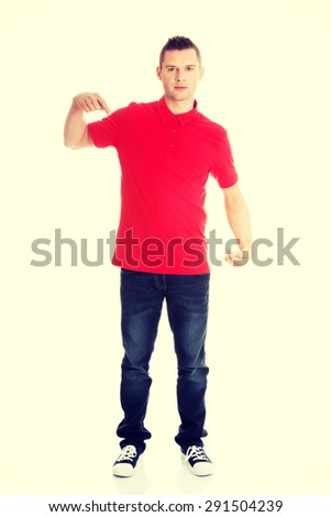 Excited man pointing on copy space on his tshirt - stock photo