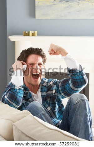 Excited Man Sitting On Sofa At Home Talking On Phone - stock photo