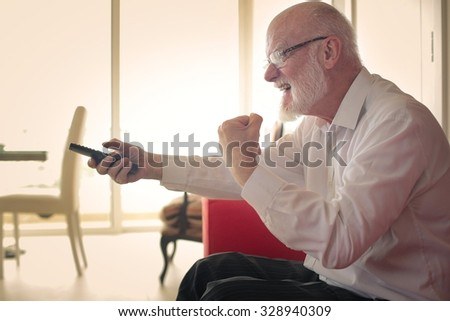 Excited man watching tv - stock photo