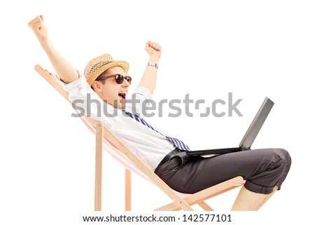Excited man with laptop sitting on a beach chair, isolated on white background - stock photo