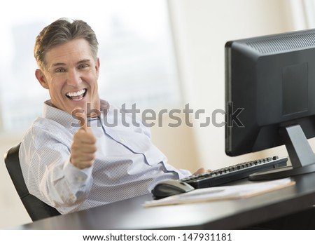 Excited mature businessman gesturing thumbs up while sitting at computer desk in office - stock photo