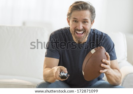Excited mature man with American football watching TV on sofa - stock photo