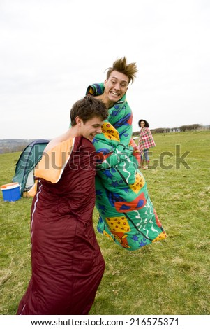 Excited men jumping in sleeping bags at outdoor festival - stock photo