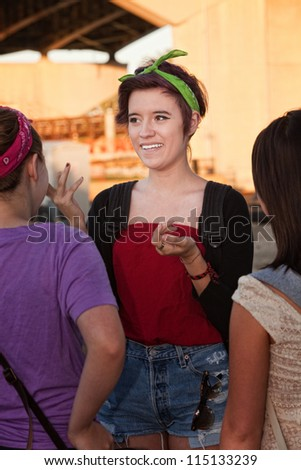 Excited Mexican teenage girl with friends outdoors - stock photo