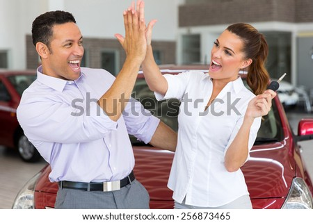 excited mid age couple giving high five after buying new car - stock photo