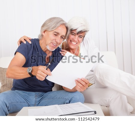 Excited middle-aged couple sitting on a couch reading a document together which contains good news