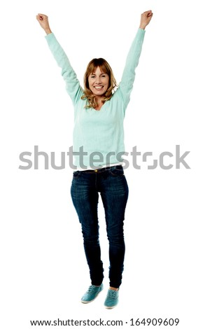 Excited middle aged woman raising her arms - stock photo