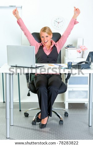 Excited modern business woman sitting at office desk and rejoicing her success - stock photo