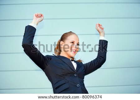Excited modern business woman standing at office building  and rejoicing her success