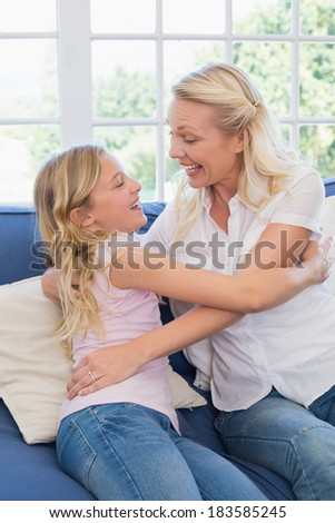 Excited mother embracing daughter while sitting on sofa in living room