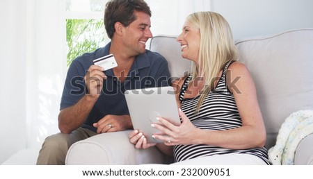 Excited parents smiling at camera with credit card
