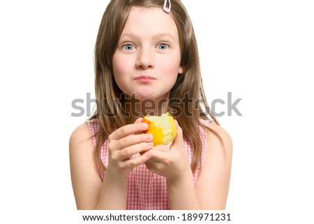 Excited playful young girl eating a fresh ripe golden apple looking at the camera with wide eyes as she bites into it, head and shoulders studio portrait - stock photo