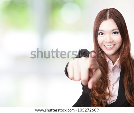 excited Portrait of a successful business woman pointing at you and smiling with green background, model is a asian beauty - stock photo
