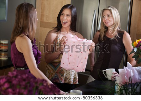 Excited pregnant lady recieves baby clothes as present from friend - stock photo