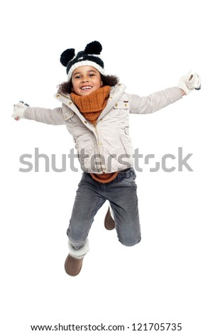 Excited primary girl jumping with joy dressed in white clothes.