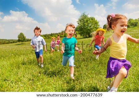 Excited running kids in green field play together - stock photo