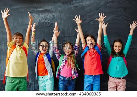 Excited schoolchildren standing with hands up - stock photo