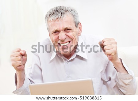 Excited senior business man working on a laptop indoor