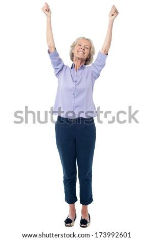 Excited senior citizen raising her hands - stock photo
