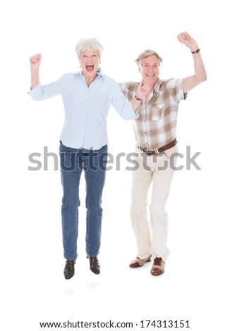 Excited Senior Couple Raising Hand Over White Background - stock photo