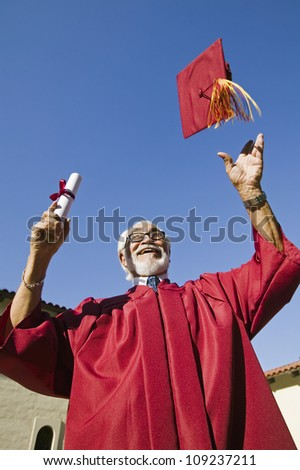 Excited senior male graduate throwing mortarboard against sky - stock photo