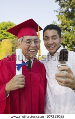 Excited senior male graduate with son taking self-portrait through cell phone - stock photo