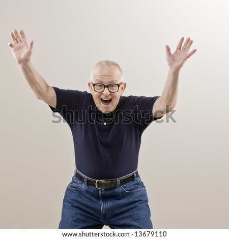 Excited senior man with arms raised - stock photo