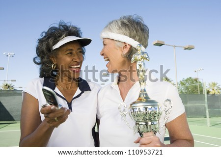 Excited senior tennis players with trophy checking self portrait on cell phone - stock photo