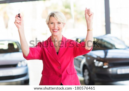 excited senior woman collecting her new car from dealership - stock photo