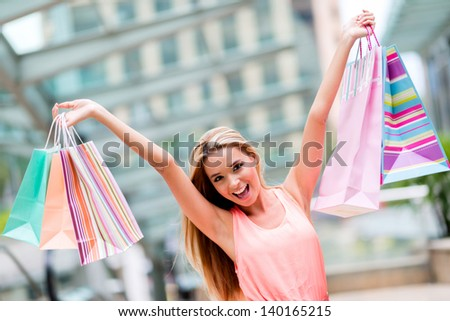 Excited shopping woman holding bags with arms up - stock photo