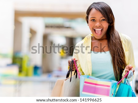 Excited shopping woman looking at her purchases - stock photo