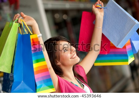 Excited shopping woman with bags at a mall - stock photo