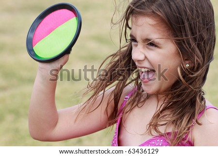 Excited small girl playing catch and laughing with a diffused green background - stock photo