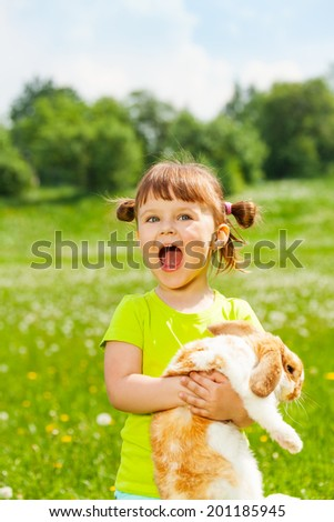 Excited small girl with open mouth hugging rabbit
