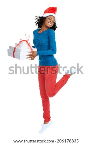 Excited smiling african female with santa hat and stack of gifts jumping in studio - stock photo