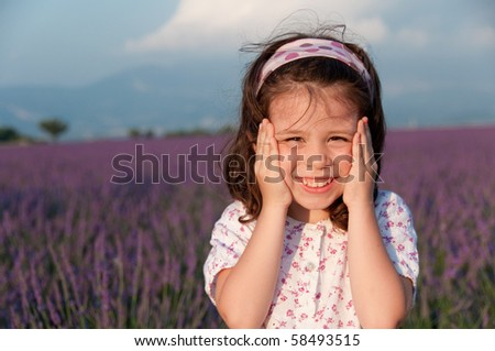 Excited smiling little girl with her hands on her face against a lavender field - stock photo